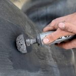 Worker using tire grinder machine for tire repairing